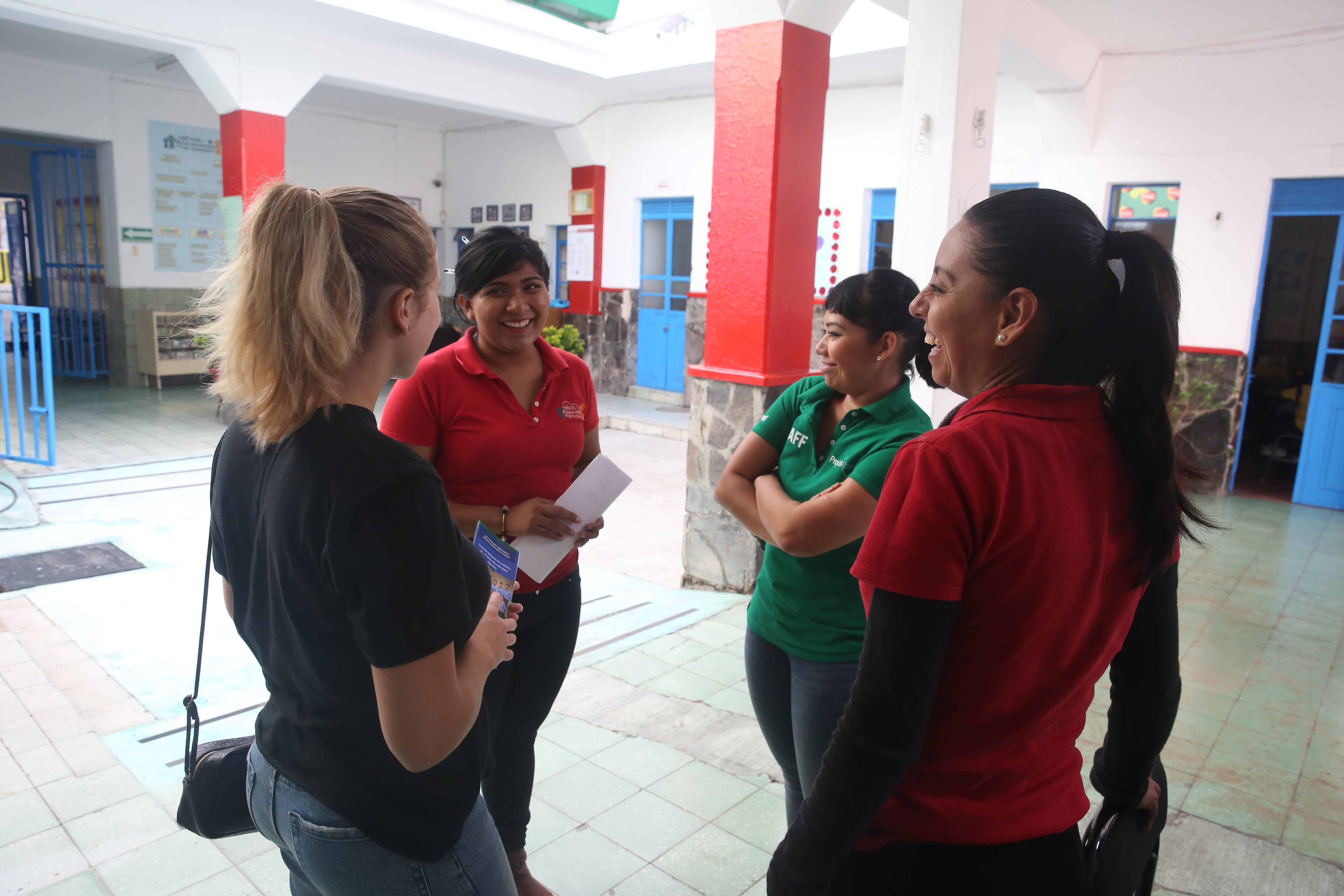 Female International Development interns stand in Day Centre prior to their progress meeting during their internship in Mexico.